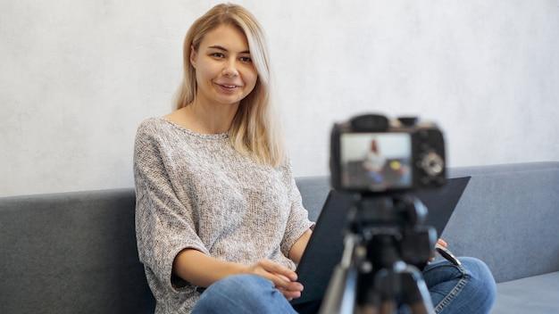 カメラを見ているラップトップを持つ若い女性ブロガー。彼女はビジネスについて話したり、学生向けの講義を録音したりします。彼女は前向きで笑顔です。