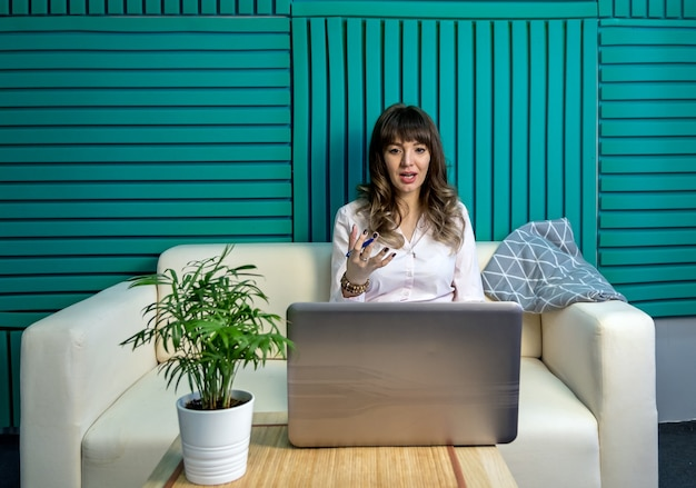 Young female blogger works with a laptop online. the concept of remote learning.