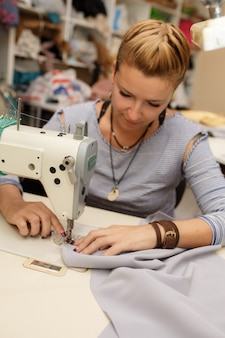 Young female blonde dressmaker cloth designer works on sewing machine