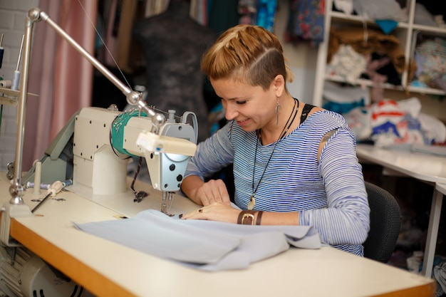 Young female blonde dressmaker works on sewing machine. dress manufacturing industry