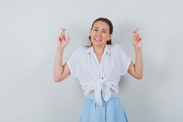 Giovane donna in camicetta, gonna tenendo le dita incrociate e guardando speranzoso