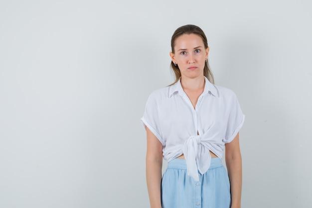 Giovane donna in camicetta e gonna guardando davanti e guardando concentrato, vista frontale.