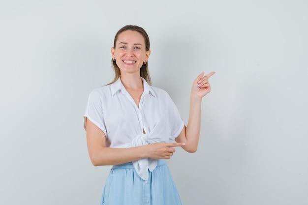 Giovane donna in camicetta, gonna rivolta da parte e guardando fiducioso