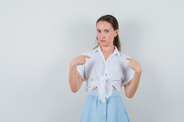 Giovane donna in camicetta, gonna che punta a se stessa e che sembra confusa