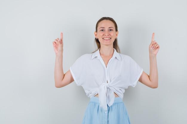 Giovane donna in camicetta, gonna rivolta verso l'alto e che sembra felice