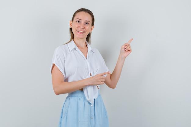 Giovane donna in camicetta e gonna che punta all'angolo in alto a destra e sembra allegra