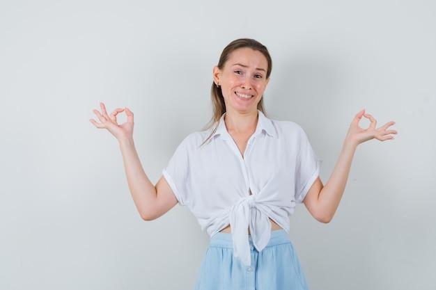 Giovane donna in camicetta, gonna che mostra gesto di meditazione e sembra allegra