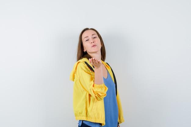 Giovane donna che soffia aria bacio con labbra imbronciate in t-shirt, giacca e dall'aspetto carino. vista frontale.