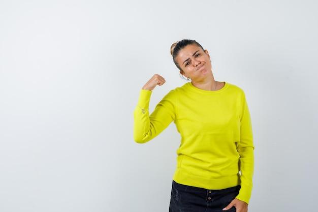 Giovane femmina che soffia le guance in maglione, gonna di jeans e sembra divertente