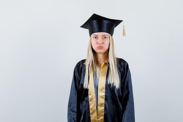 Giovane femmina che soffia le guance mentre guarda la telecamera in uniforme da laureato e sembra delusa.