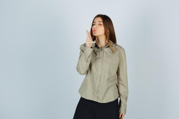 Giovane donna che soffia sulla pistola del dito con le labbra imbronciate in camicia, gonna e sembra sicura. vista frontale.