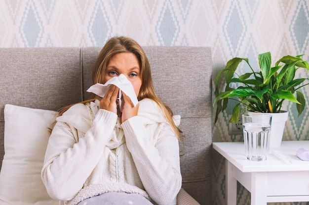 Young female blows her nose holding tissue handkerchief, having symptoms of cold
