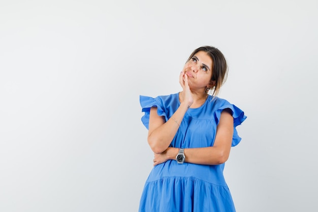 Giovane donna in abito blu che guarda in alto e sembra pensierosa