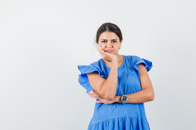 Giovane donna in abito blu in piedi in posa pensante e dall'aspetto ragionevole