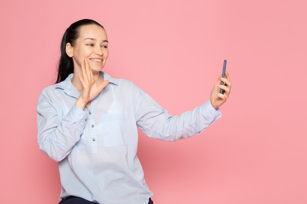 Young female in blue shirt posing using a phone on the pink wall