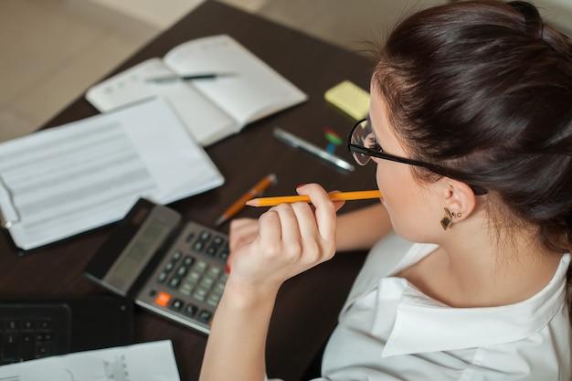Молодая женщина-бухгалтер считает на калькуляторе