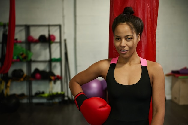 Young female boxer, sporty girl, athlete woman, sports woman, wearing red boxing gloves, looks at camera posing against sports equipment at the gym