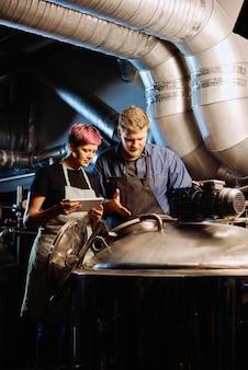 디지털 태블릿이 있는 젊은 여성 양조업자는 큰 작업장 내에서 맥주 준비를 위한 장비를 사용하는 동안 남성 동료 옆에 서 있습니다.