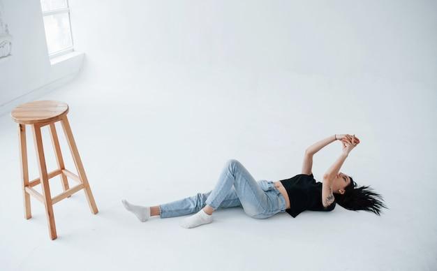 La giovane teenager bruna femminile ha un servizio fotografico in studio durante il giorno
