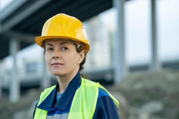建設現場でヘルメットと制服を着た若い女性ビルダー