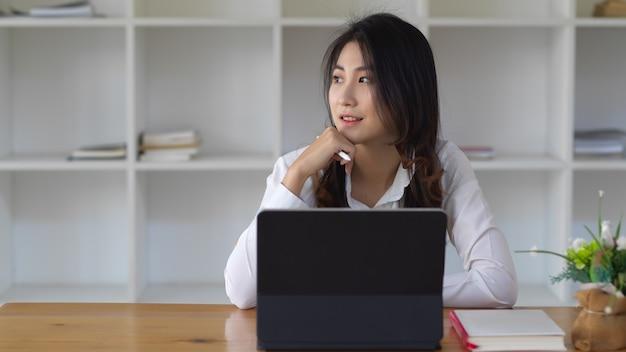 Молодой женский бизнес-работник, работающий с планшетом, глядя на окна