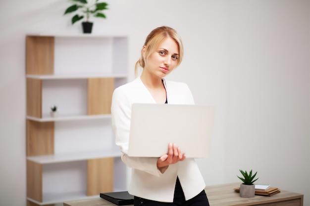 노트북에 그녀의 사무실에서 일하는 젊은 여성 사업가