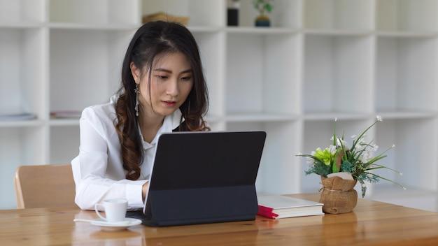 Молодая женщина-предприниматель, работающая над своим проектом с планшетом
