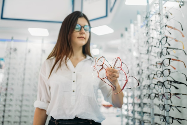 Young female buyer holds many glasses in hand