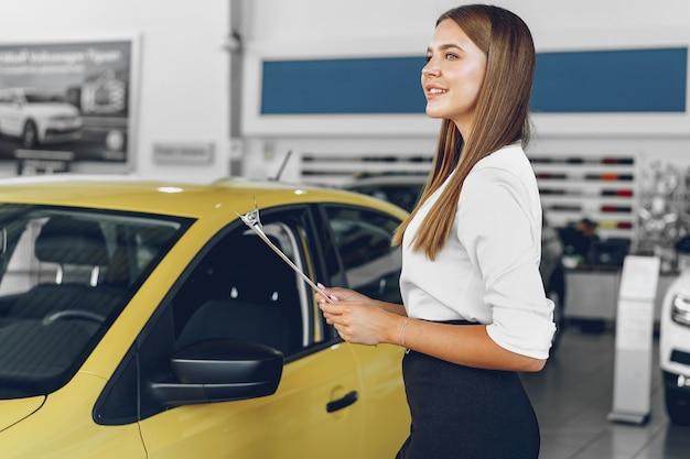 Молодая женщина-автодилер стоит в автосалоне возле новой машины