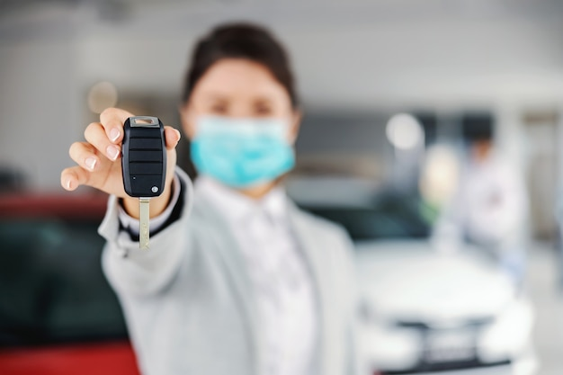 Young female car seller with face mask standing in car salon and showing car keys.