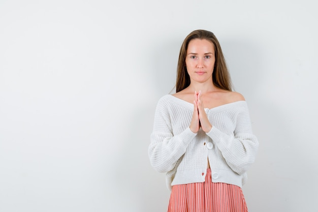 Young female in cardigan and skirt holding hands in praying gesture isolated