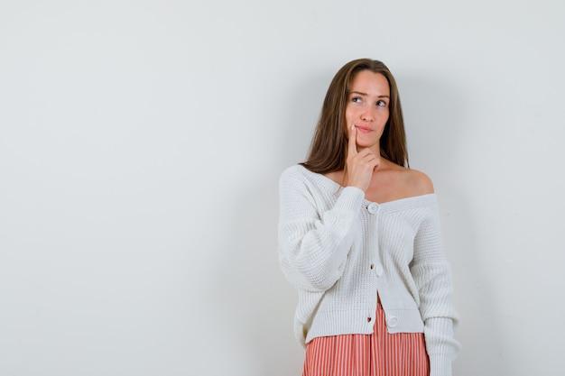 Giovane donna in cardigan e gonna mantenendo il dito sul mento cercando pensieroso isolato
