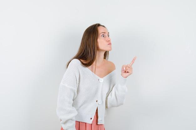 Giovane donna in cardigan e gonna che punta all'angolo superiore destro che sembra arrabbiato isolato