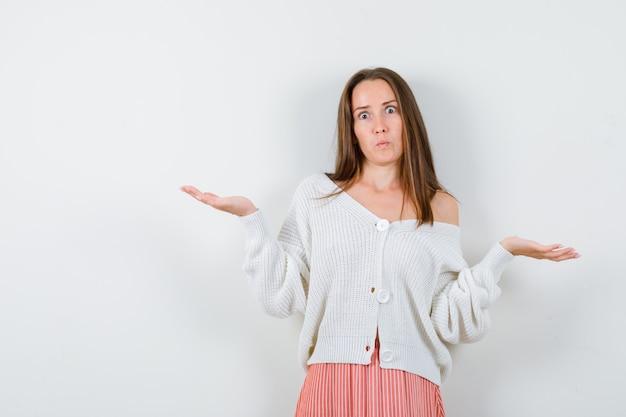 Giovane donna in cardigan e gonna che mostra gesto impotente isolato