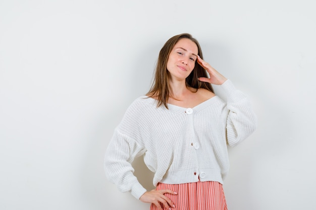 Young female in cardigan and skirt showing salute gesture looking proud isolated