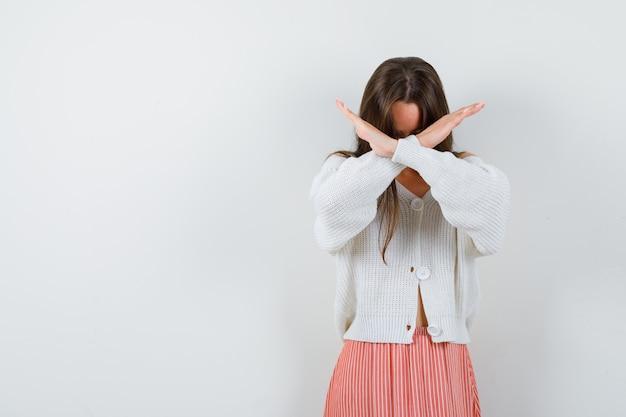 Giovane donna in cardigan e gonna che mostra il gesto di arresto cercando risoluto isolato