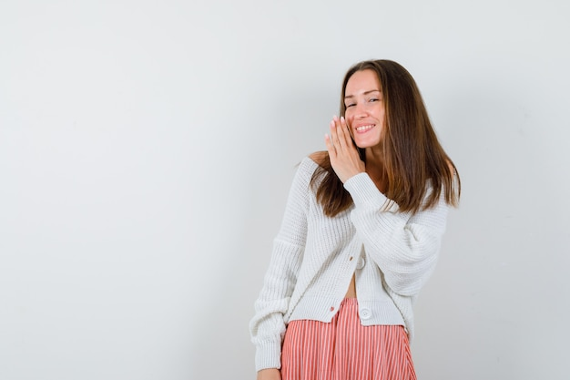 Young female in cardigan and skirt telling secret behind hand looking happy isolated