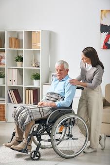 집에 머무는 동안 휠체어에 앉아 회색 머리 수석 남성 연금에 이야기하는 젊은 여성 간병인