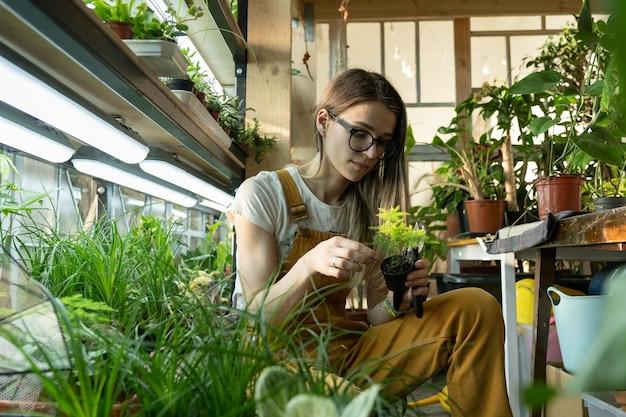 퇴근 후 화분의 젊은 여성 관리는 실내 정원 플로리스트 여성 기업가에서 휴식을 취합니다.