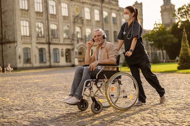 Young female care taker in protective mask spending time with senior man in wheelchair wearing