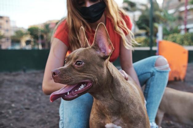 외부 얼굴 마스크를 착용하는 동안 그녀의 강아지의 뒷면을 애무하는 젊은 여성. 개에 집중