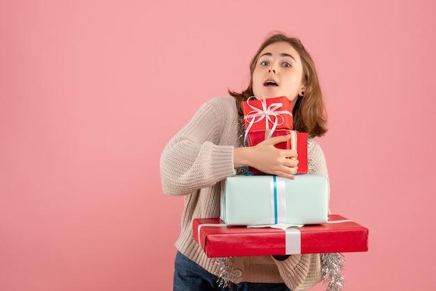 ピンクのクリスマスプレゼントを運ぶ若い女性