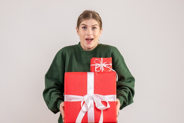 白でクリスマスプレゼントを運ぶ若い女性