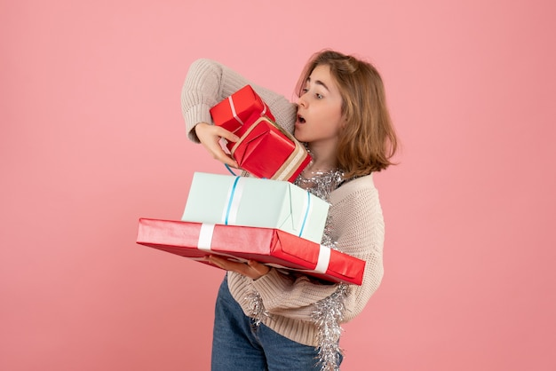 Young female carrying xmas presents on pink