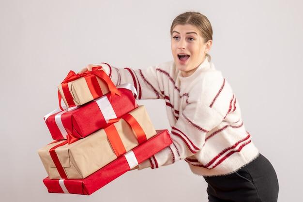 Giovane donna che trasportano regali di natale su bianco