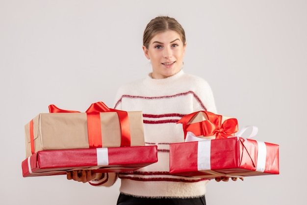 Young female carrying xmas presents on white