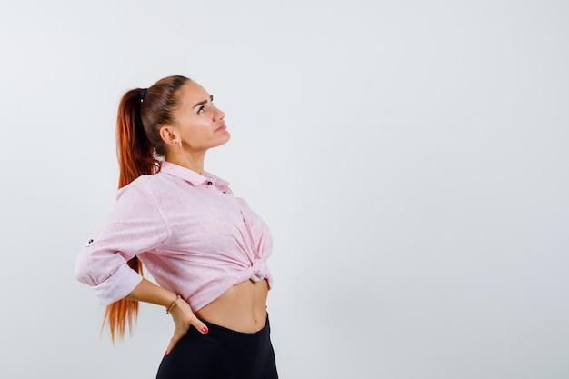 Giovane donna in camicia casual tenendo la mano dietro la schiena e guardando fiducioso, vista frontale.