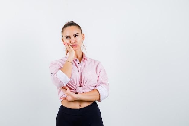 Giovane donna in camicia casual tenendo la mano sulla guancia e guardando pensieroso, vista frontale.