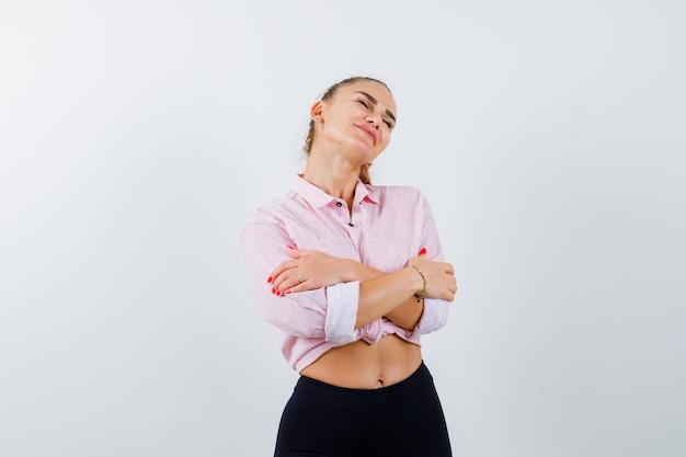 Giovane donna in camicia casual che si abbraccia e che sembra carina, vista frontale.