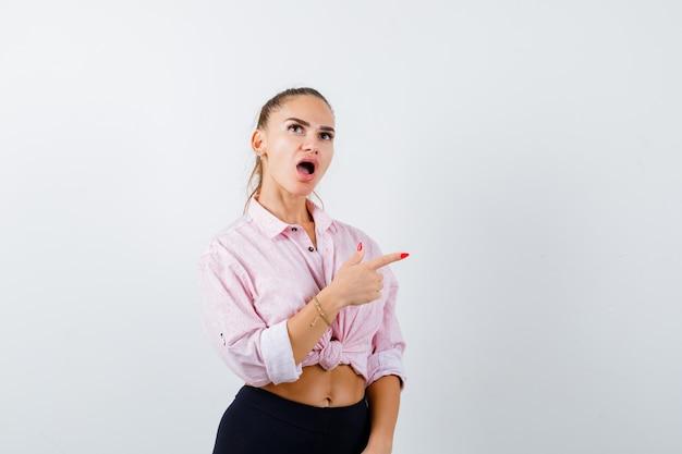Giovane donna in camicia casual che punta verso il lato destro e che sembra perplessa, vista frontale.